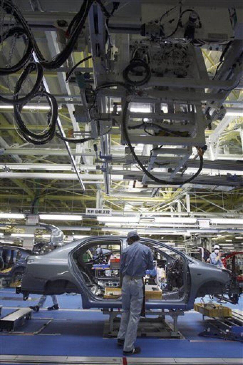 FILE _ In this photo taken Feb. 16, 2011, a worker assembles a Yaris compact sedan, set for export to North America, on a newly opened assembly line at a plant of Toyota Motor Co.'s group company Central Motor Co. in Ohira in Miyagi Prefecture, northern Japan. Toyota Motor Corp., the world's biggest automaker, said it will extend production halts at its car plants through March 22, affecting about 95,000 vehicles. (AP Photo/Koji Sasahara, file)