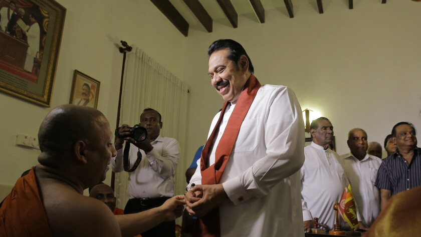 Prime Minister Mahinda Rajapaksa speaks with a Buddhist monk Saturday after signing his resignation letter at his Colombo home.