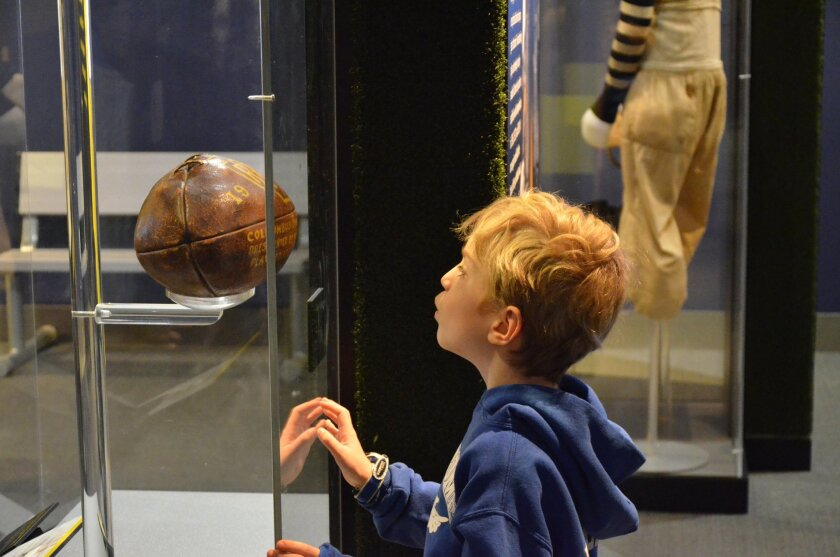 """This undated image provided by Liberty Science Center shows a young visitor at the museum looking at an artifact from an exhibit called """"Gridiron Glory."""" The Liberty Science Center is one of a number of places for Super Bowl fans to visit in New Jersey while in town for the championship game. (AP Photo/Liberty Science Center) (AP Photo/Liberty Science Center)"""