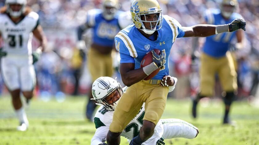 UCLA receiver Theo Howard slips the tackle of Hawaii defensive back Zach Wilson during a game in 2017.