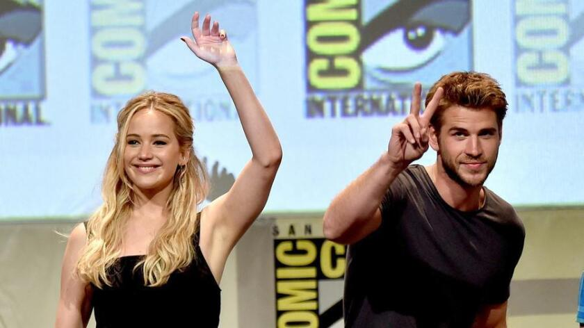 Actress Jennifer Lawrence (L) and actor Liam Hemsworth wave at the audience. (Kevin Winter / Getty Images)