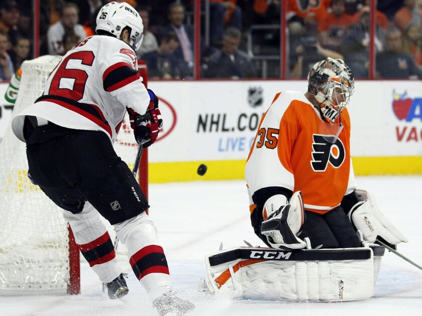 The puck goes past Philadelphia Flyers goalie Steve Mason, right, but not into the net as New Jersey Devils' Patrick Elias, left, watches during the first period of an NHL hockey game Thursday, Oct. 9, 2014, in Philadelphia. (AP Photo/Tom Mihalek)