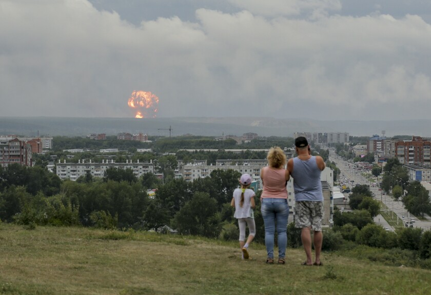 A family watches explosions in Achinsk, Russia