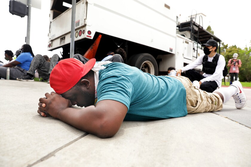 Michael O'Quinn, 45, of Compton, prays during a peaceful protest where demonstrators laid down for the amount of time that George Floyd was on the ground, outside the Cerritos Sheriff's Station in Cerritos on Monday.