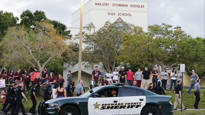 FILE - In this Feb. 28, 2018 file photo, a police car drives near Marjory Stoneman Douglas High Scho