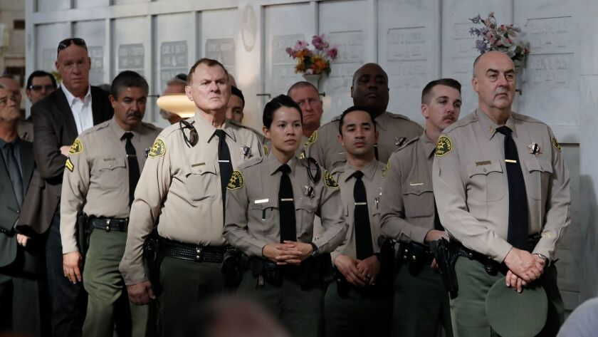 POMONA, CALIF. -- THURSDAY, FEBRUARY 8, 2018: LA Sheriff's officers listen to Pastor Kimball Colbur