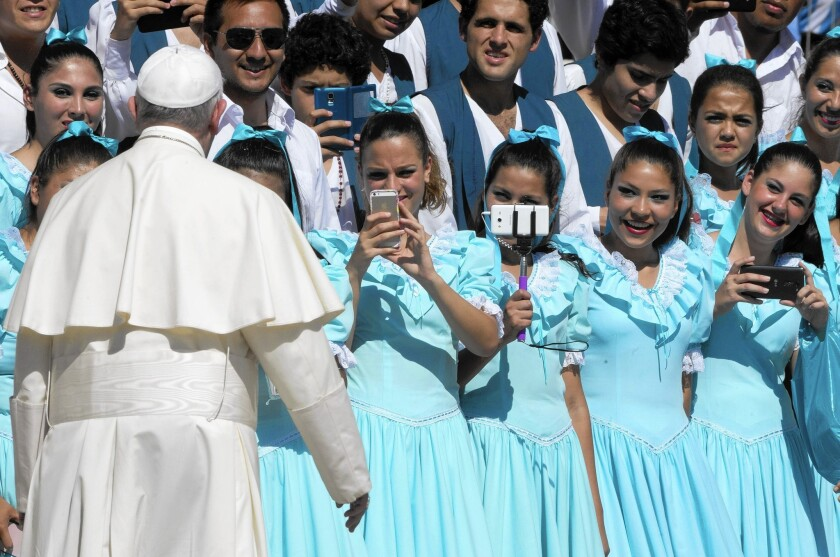 Dancers from Argentina take pictures of Pope Francis in August after his weekly general audience in St. Peter's Square at the Vatican.