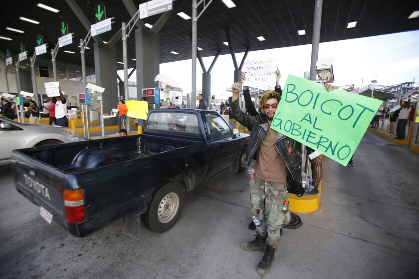 Jesus Navarro waves at cars entering Mexico on Jan. 8 during a protest at the El Chaparral Port of Entry.