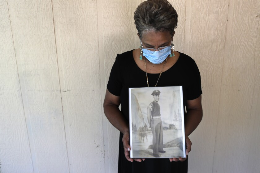 In this Monday, May 18, 2020 photo, Belvin Jefferson White poses with a portrait of her father Saymon Jefferson at Saymon's home in Baton Rouge, La. Belvin recently lost both her father and her uncle, Willie Lee Jefferson, to COVID-19. (AP Photo/Gerald Herbert)