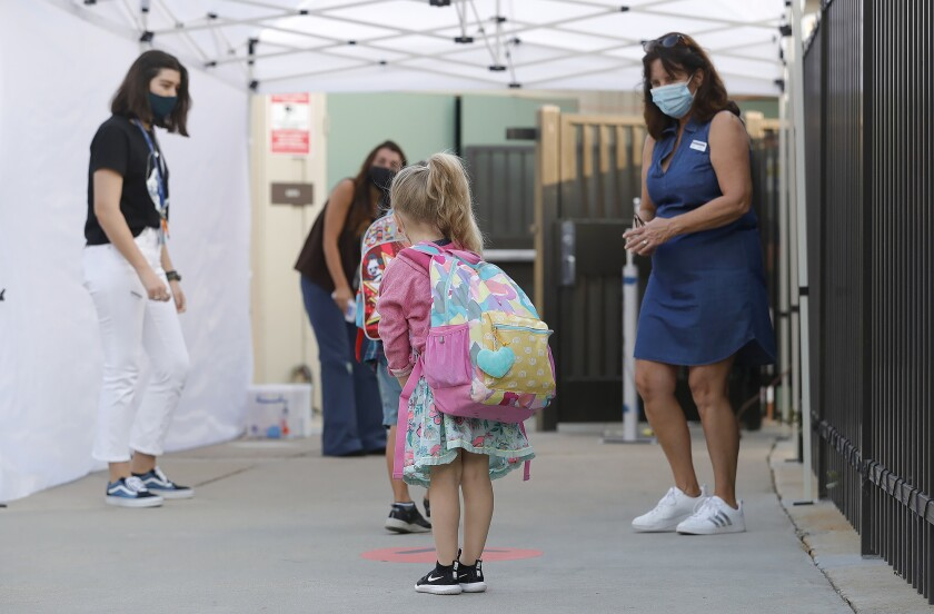 A kindergartner is greeted at a pre-screen station at Top of the World Elementary in October 2020.