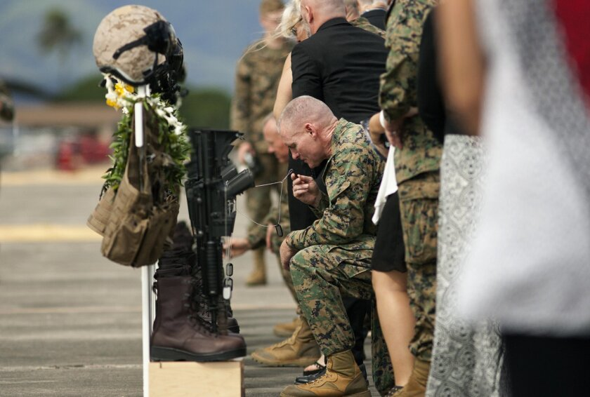 Family, friends and comrads pay their respects during a memorial service for the 12 U.S. Marines who died when their helicopters crashed off the North Shore of Oahu, Hawaii, Friday, Jan. 22, 2016, at Marine Corps Base Hawaii. Servicemen draped flight gear on 12 white crosses Friday to commemorate the Marines who died when two helicopters crashed off the coast of Hawaii during a nighttime training mission. Military members and families gathered for the memorial service at Marine Corps Base Hawaii in Kaneohe after the status of the dozen missing Marines changed to deceased following five days of searching. (AP Photo/Caleb Jones)