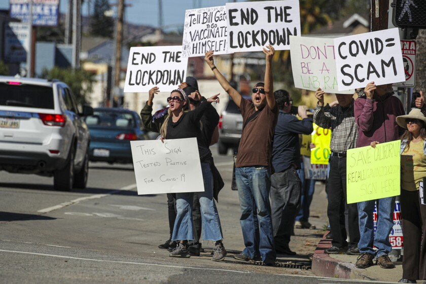 Protesters with signs that say End the Lockdown and COVID equals scam