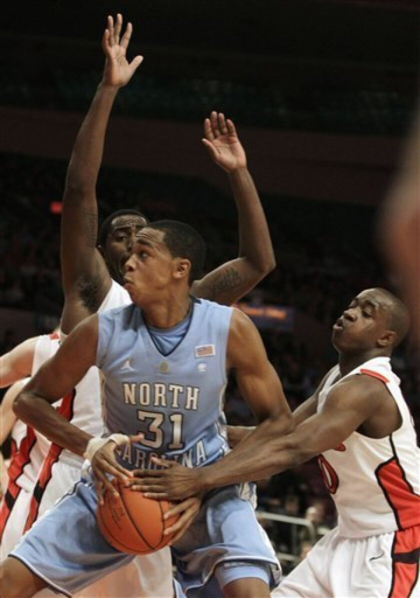 Rutgers forward Jonathan Mitchell, rear, defends as guard James Beatty, right, forces the ball from the hands of North Carolina forward John Henson (31) in the first half of an NCAA college basketball game at Madison Square Garden in New York, Tuesday, Dec. 28, 2010. (AP Photo/Kathy Willens)