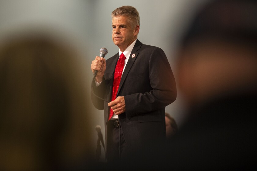 U.S. Rep. Kirk Cox holds a microphone