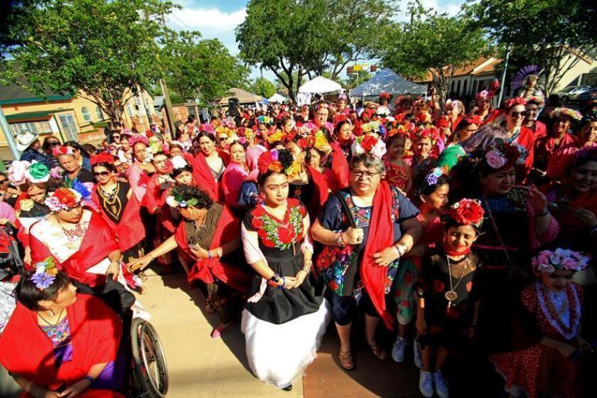 Cerca de 300 personas vestidas con los típicos y multicolores atuendos que caracterizaron a la pintora mexicana Frida Kahlo se congregan hoy, sábado 14 de abril de 2018, para imponer el primer récord mundial del mayor número de individuos vestidos como la pintora mexicana, en Houston, Texas (EE.UU.). EFE
