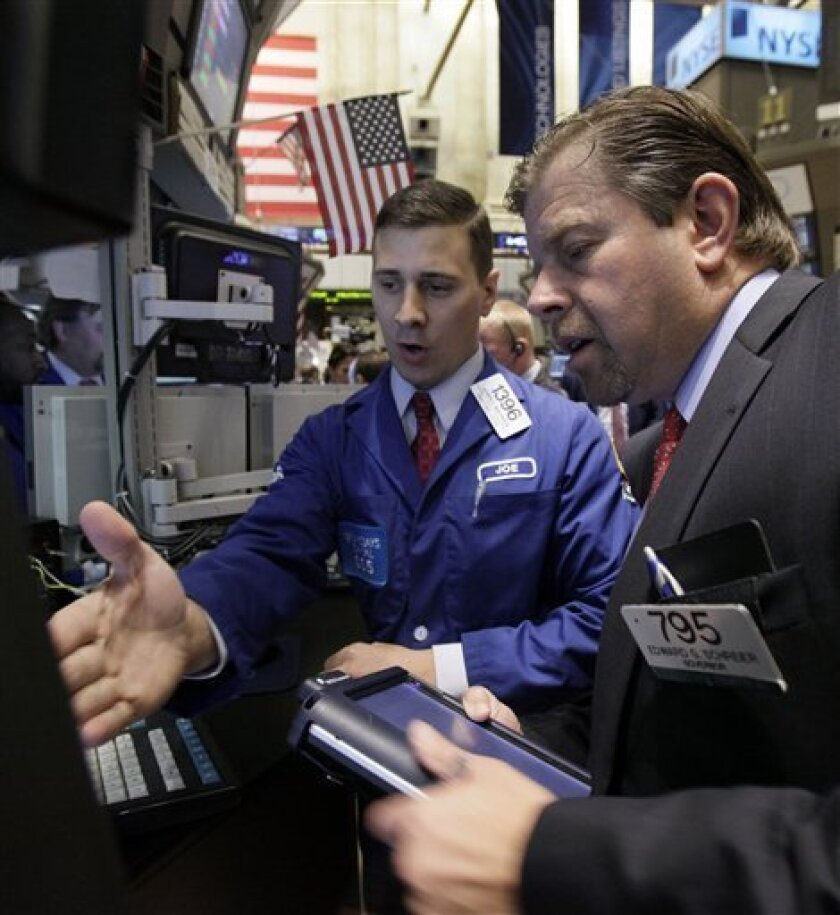 Specialist Joseph Mastrolia, left, and trader Edward Schreier work on the floor of the New York Stock Exchange Friday, Oct. 8, 2010. (AP Photo/Richard Drew)