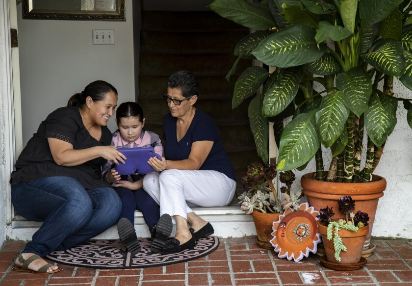 Mabel Gonzalez, left, her daughter Camila, 8, and mother, Teresa, FaceTime with Gonzalez's father, Francisco.