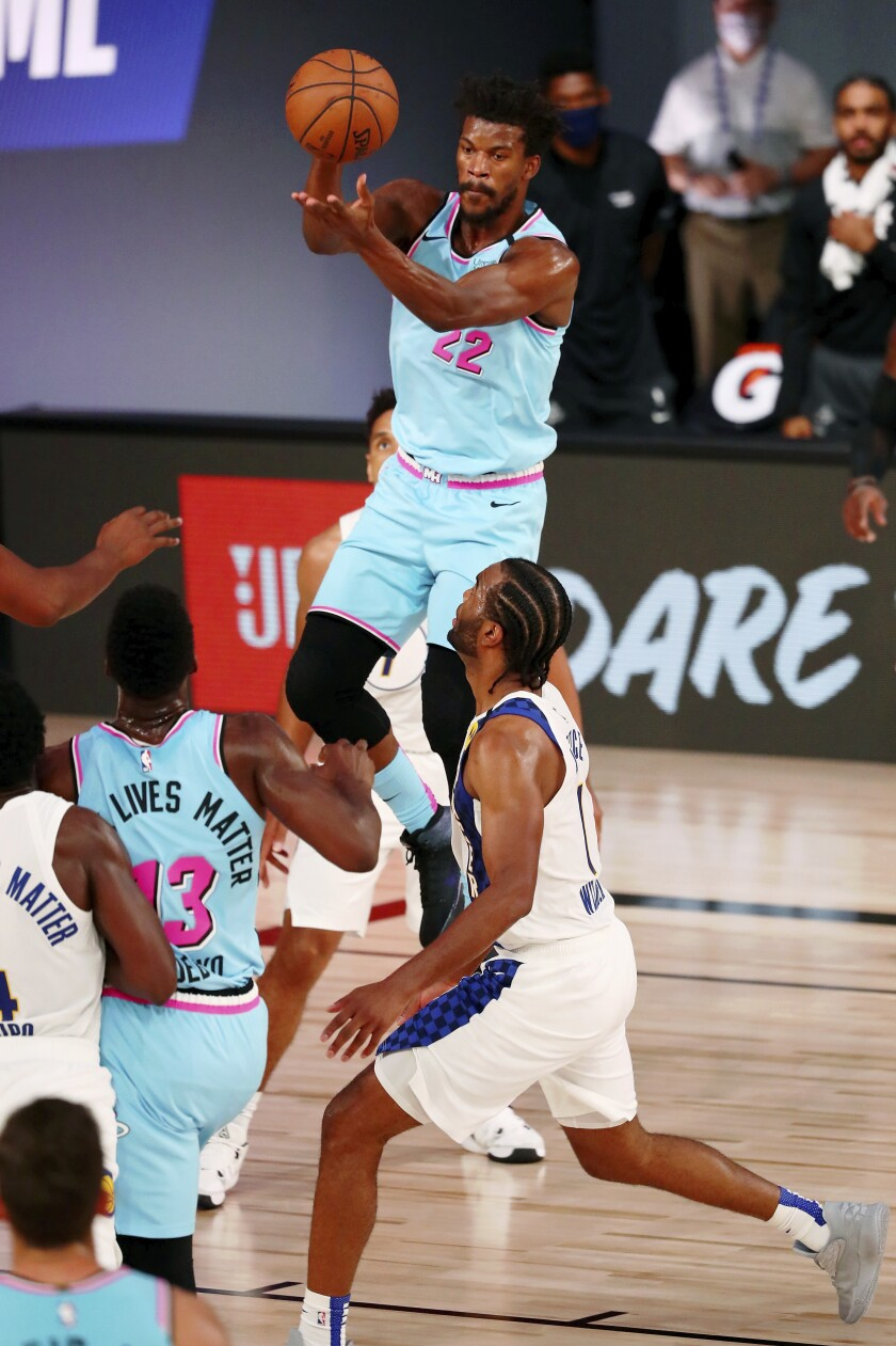 Miami Heat forward Jimmy Butler (22) makes a jumping pass against the Indiana Pacers during the second half of an NBA basketball game Monday, Aug. 10, 2020, in Lake Buena Vista, Fla. (Kim Klement/Pool Photo via AP)