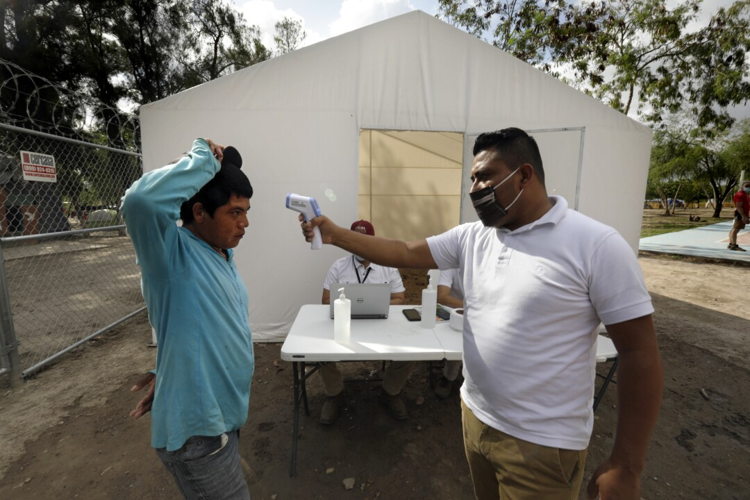 A man has his temperature taken at the camp in Matamoros, Mexico.