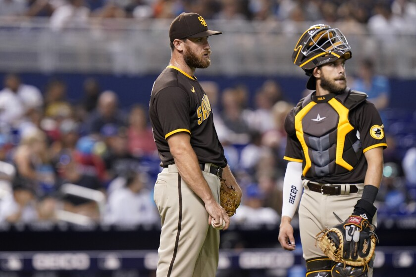 Austin Adams stands with catcher Austin Nola after hitting the Miami Marlins' Jon Berti with a pitch