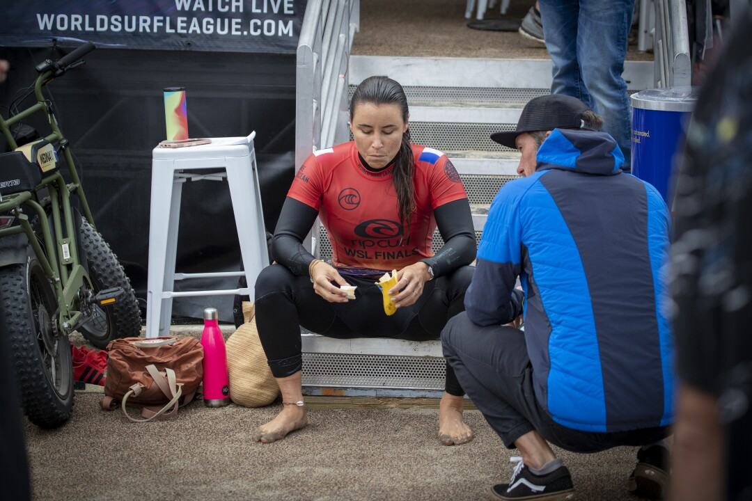 Johanne Defay eats a banana and rests after beating sevem-time WSL champion Stephanie Gilmore