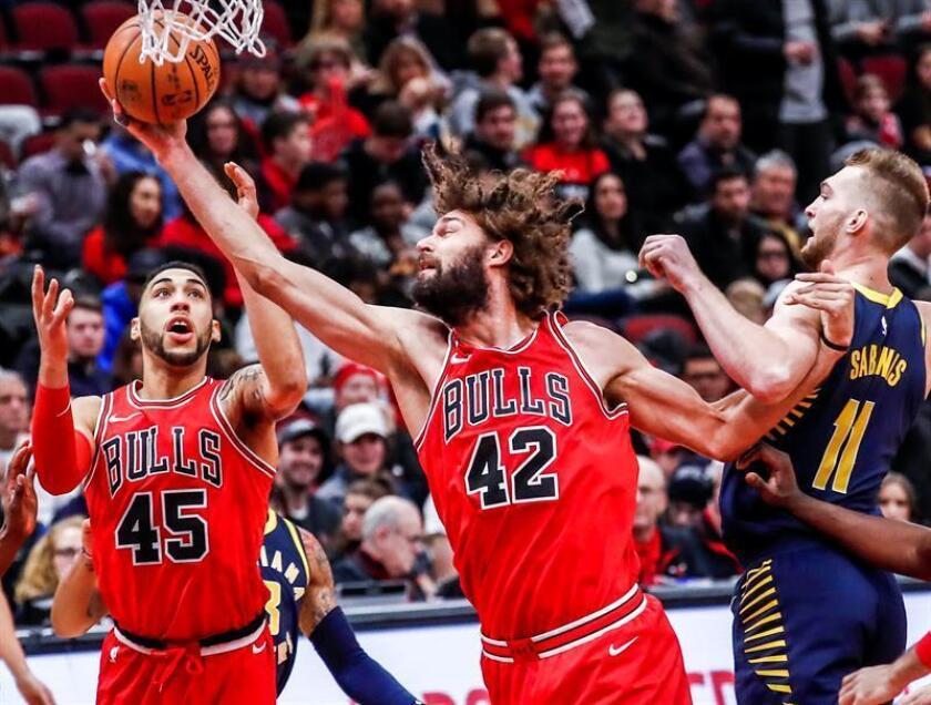Robin Lopez (c), pívot de los Bulls de Chicago, fue registrado este viernes al intentar dominar un balón, ante la mirada de su compañero Denzel Valentine y la marca del lituano Domantas Sabonis, de los Pacers de Indiana, durante un partido de la NBA, en el United Center de Chicago (Illinois, EE.UU.) EFE