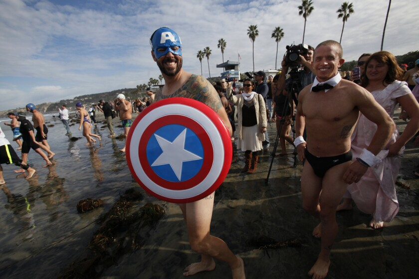 In 2013 Mike Kelley, aka Captain America, took the plunge with about 150 close friends at La Jolla Shores on the first day of the year. He has been doing the polar bear swim since he was a boy, he said. To the right is Jay Weber, who wore a tuxedo collar for the event. (Peggy Peattie/U-T)
