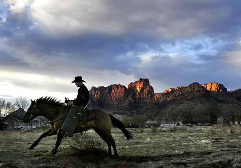 A young man claiming to be a local town security guard rides through an empty lot at sunset in Colorado City, Ariz.