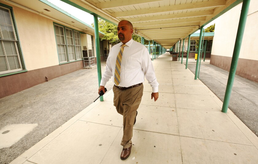 Peter Benefiel, Principal at Daniel Webster Middle School, walks on the school grounds Wednesday May