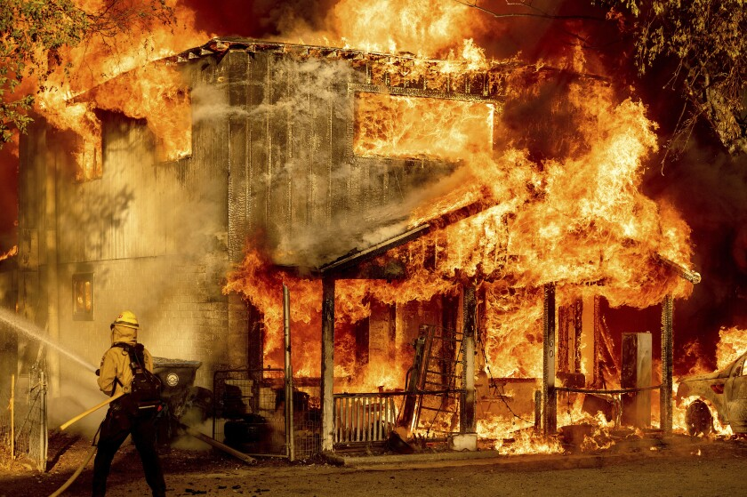 A firefighter sprays water while a home burns