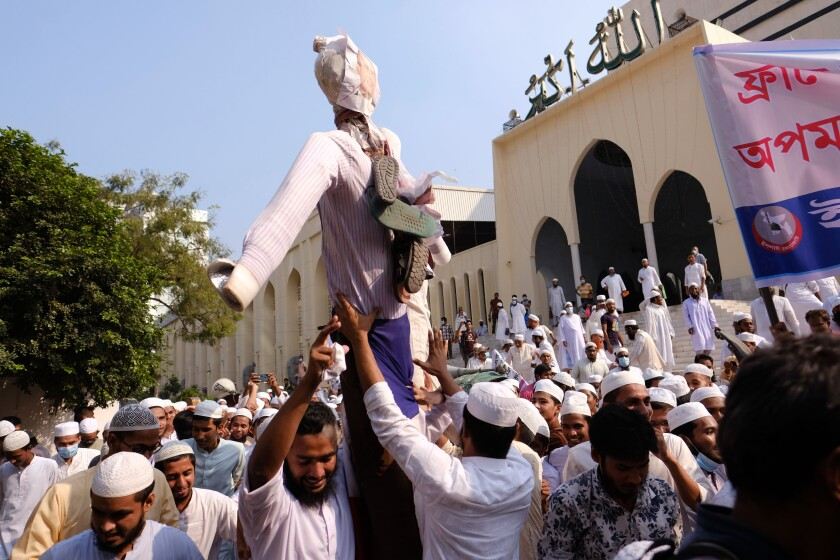 """Supporters of Islami Oikya Jote, an Islamist political party, hold up an effigy representing French President Emmanuel Macron during a protest against the publishing of caricatures of the Prophet Muhammad they deem blasphemous, in Dhaka, Bangladesh, Wednesday, Oct. 28, 2020. Muslims in the Middle East and beyond on Monday called for boycotts of French products and for protests over the caricatures, but Macron has vowed his country will not back down from its secular ideals and defense of free speech. Posters read """"France is the enemy of humanity. World citizens fight back."""" second left, """"Muslims of the world stand against insults to the prophet,"""" third right and """"Stop buying products from France. In the name of the Prophet,"""" left. (AP Photo/Mahmud Hossain Opu)"""