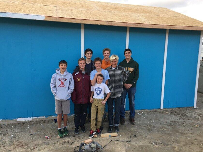 George champion (in orange) and helpers Aidan Holden, Casey Holden, Patrik Kjos, Nick Holden, Arthur Champion, Max Gibbs, and Joey D'angelo, pose for a photo after building the house in Mexico.