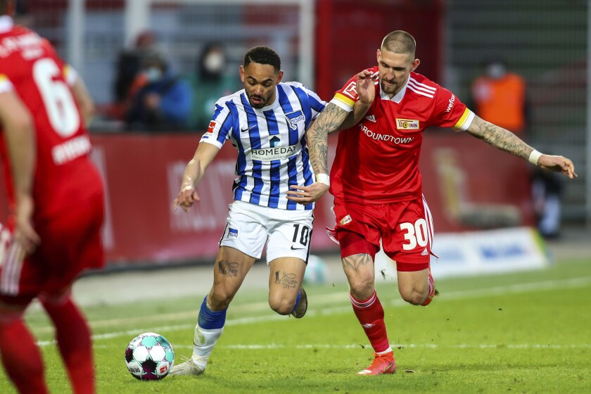 Hertha's striker Matheus Cunha, left, and Union's midfielder Robert Andrich during their German Bundesliga soccer match in Berlin, Germany, Sunday April 4, 2021. Union Berlin denied Hertha Berlin an important win as they battled to a hard-fought 1-1 draw in the Bundesliga, in its battle against relegation and Hertha reciprocated by denting its city rival's hopes of European qualification. (Andreas Gora/Pool via AP)
