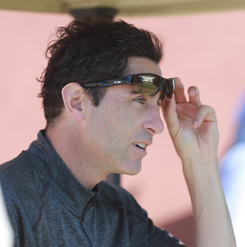 Padres General Manager A.J. Preller watches pitchers throw in the bullpen during Padres spring training