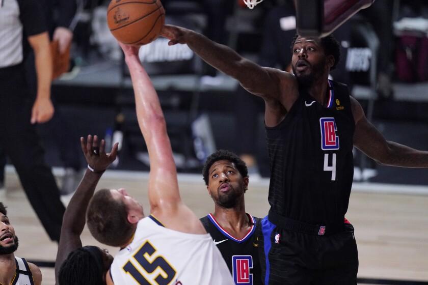 Denver Nuggets center Nikola Jokic is blocked by Clippers forward JaMychal Green.