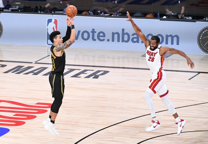 Lakers guard Danny Green misses a late three-point shot in front of Miami Heat defender Andre Iguodala.