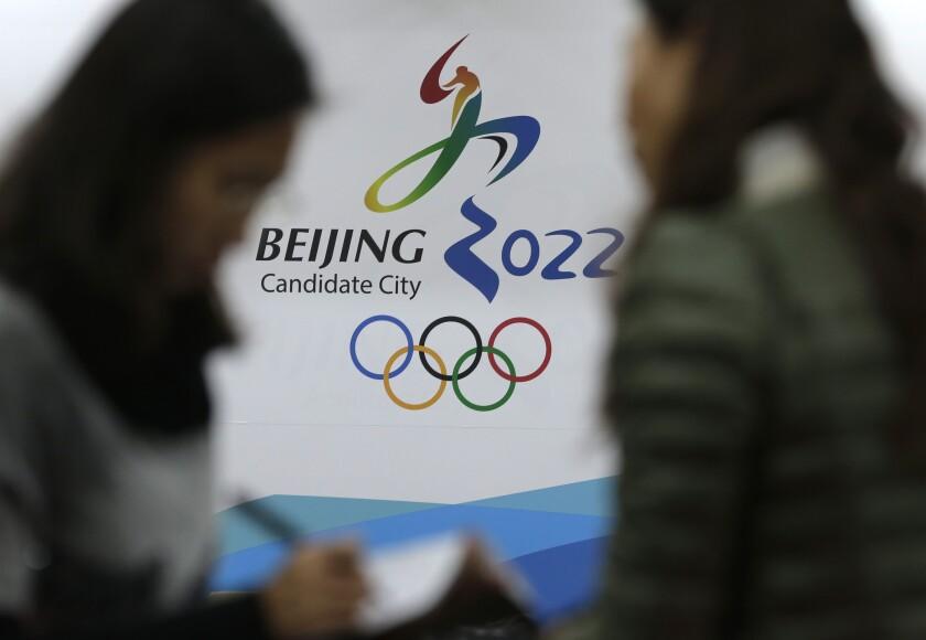 Periodistas conversan frente al logo de la candidatura de Beijing para los Juegos Olímpicos de Invierno 2022