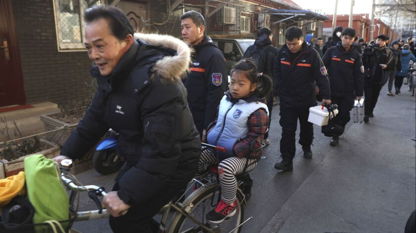 A man rides with a student past crime scene investigators Jan. 8 as they leave the Beijing No. 1 Affiliated Elementary School of Xuanwu Normal School.