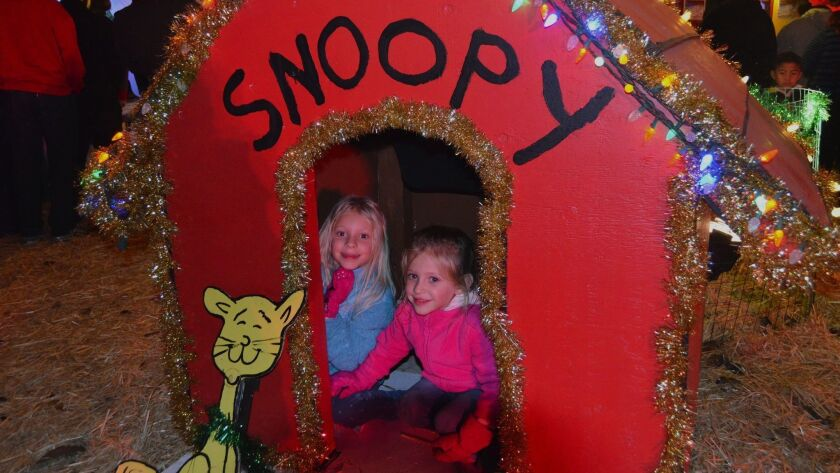 Sisters, Bella, left and Bailey_Bodalvi crawled around in Snoopy's dog house during the grand openin