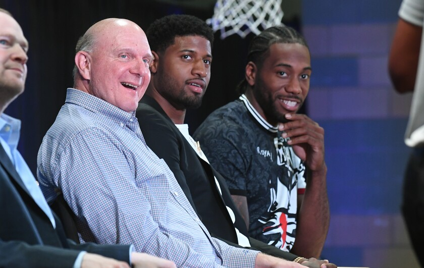 Clippers owner Steve Balmer with new players Paul George, center, and Kawhi Leonard at Green Meadows Recreation Center in Los Angeles in July.