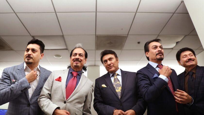 Los Tigres del Norte gussy themselves up in a green room at the Hollywood Bowl. They are, from left, Luis Hernandez, Hernán Hernandez, Jorge Hernandez, Eduardo Hernandez and Oscar Lara.