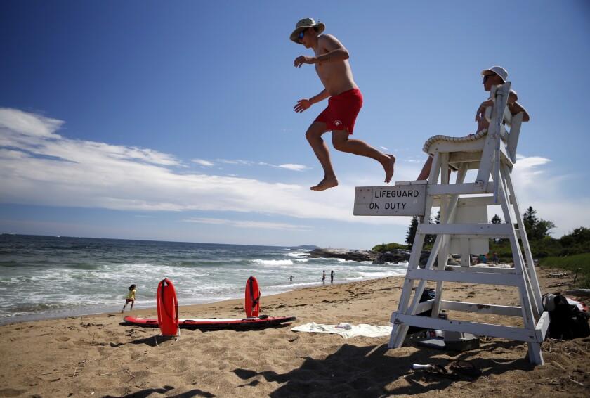 Los salvavidas Nate Samson, de 18 años, de Brunswick, Maine, a la izquierda, y Kyle Hummel, de 19, de Bath, Maine, cuidan una sección de la playa Mile en el Parque Estatal Reid en Georgetown, Maine. (AP Foto/Robert F. Bukaty)