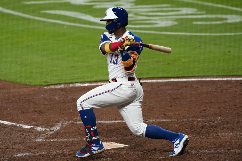 Atlanta Braves' Ronald Acuna Jr. (13) follows through on a double in the sixth inning of a baseball game against the Philadelphia Phillies, Friday, April 9, 2021, in Atlanta. (AP Photo/John Bazemore)