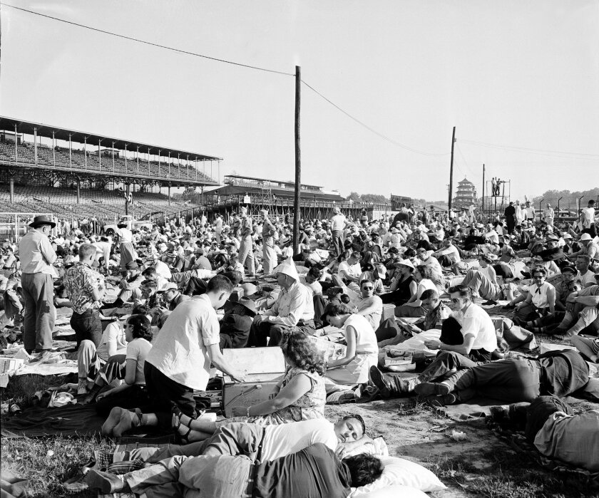 FILE - In this May 30, 1953, file photo, early arrivals at the Indianapolis Motor Speedway track lounge around on the grass in the infield of the oval Brickyard before the start of the 37th Indianapolis 500 auto race in Indianapolis, Ind. (AP Photo/File)
