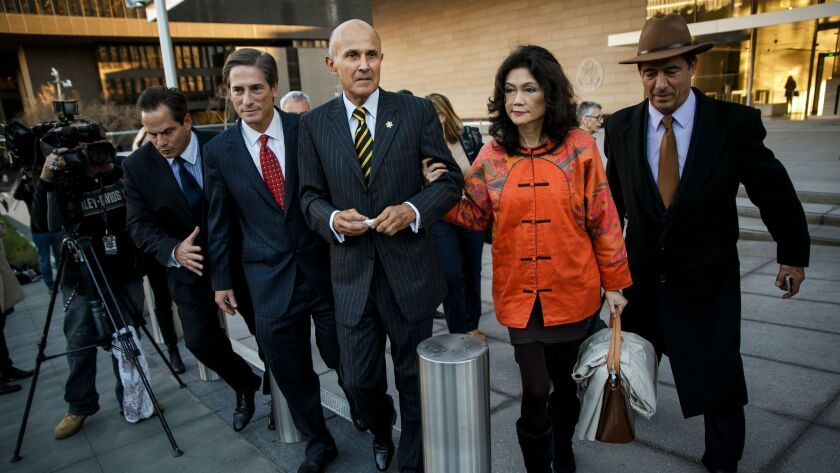Former Los Angeles County Sheriff Lee Baca, center, escorted by his wife, Carol, right, and his attorney, Nathan Hochman, center left, walks out of a federal courthouse in Los Angeles after Baca's obstruction trial ended in a mistrial.