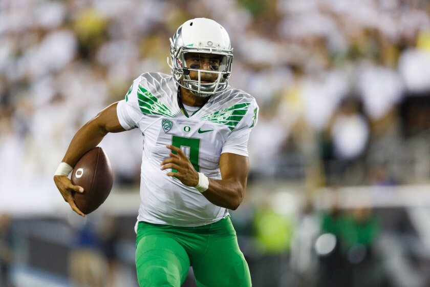 Oregon quarterback Marcus Mariota runs the football during the second quarter of an NCAA college football game against South Dakota in Eugene, Ore., Saturday, Aug. 30, 2014. (AP Photo/Ryan Kang)