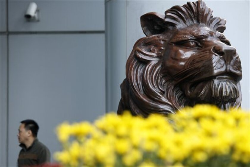 A man walks past a lion statue outside the headquarter of HSBC Holding in Hong Kong Thursday, Jan. 15, 2009. Analysts said HSBC Holdings PLC, Europe's largest bank, may have to raise US$20 billion to US$30 billion and slash its dividend. (AP Photo/Vincent Yu)