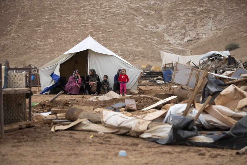 """Palestinian women and children sit front a tent in Khirbet Humsu in Jordan Valley in the West Bank, Friday, Nov. 6, 2020. Israeli troops with bulldozers and heavy equipment demolished 18 tents and other structures that housed 74 people, including 41 minors, according to the Israeli rights group B'Tselem. COGAT, the Israeli military body in charge of civilian affairs in the West Bank, said an """"enforcement activity"""" was carried out against seven tents and eight pens that were """"illegally constructed"""" in a firing range. (AP Photo/Majdi Mohammed)"""