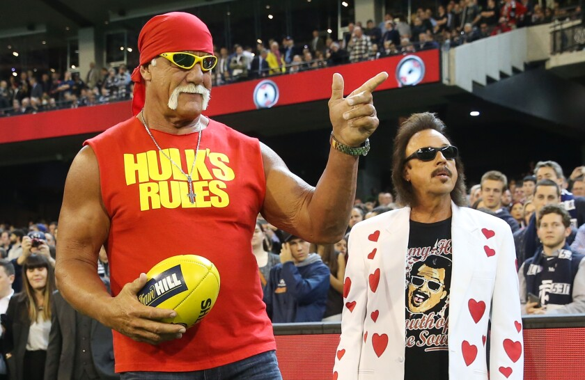 Hulk Hogan gestures to the crowd while attending an AFL game in Australia with Jimmy Hart in 2015.