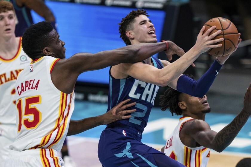 Atlanta Hawks center Clint Capela (15) fouls Charlotte Hornets guard LaMelo Ball (2) during the second half of an NBA basketball game in Charlotte, N.C., Saturday, Jan. 9, 2021. (AP Photo/Jacob Kupferman)